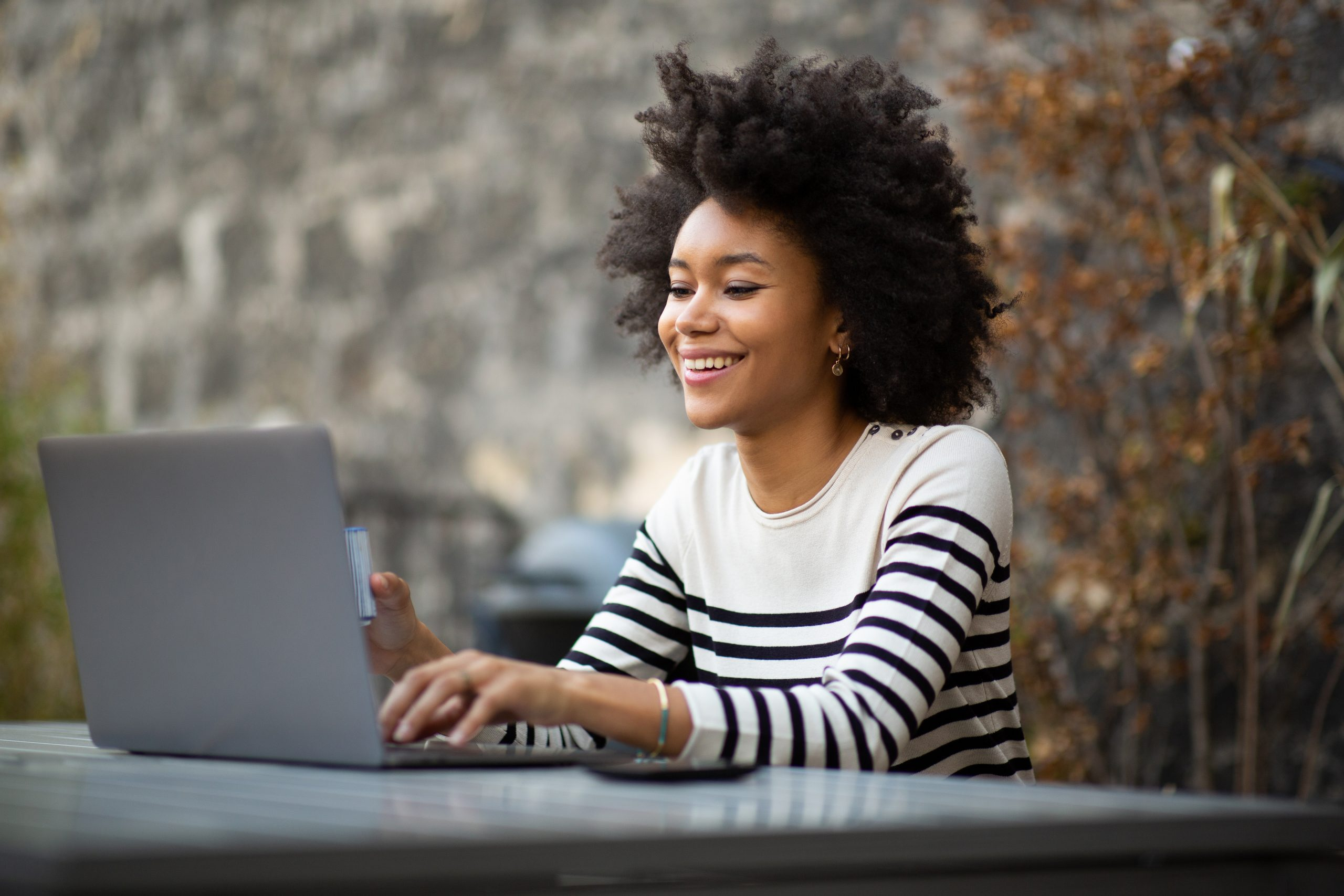 smiling young african american woman using laptop computer